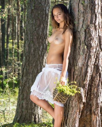 Slava, Belarusian brunette, leans against the rough bark of a tree